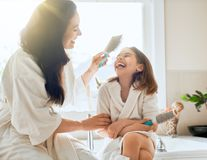 Mother and daughter combing hair Stock Photography