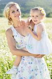 Happy family mother and daughter in field of daisy flowers Royalty Free Stock Photos