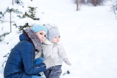 Happy family. Mother and daughter hug in winter. Mother and little daughter walking in a winter park. Mother and daughter hug at the tree. Happy . Childhood and royalty free stock photography
