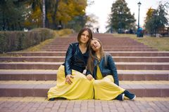 Mother and daughter leaned against each other sitting on the stairs in the park. mother`s day concept stock image
