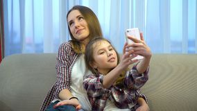 Family mother daughter leisure pastime selfie. Happy family. mother daughter leisure moments. fun pastime. young mom and girl posing for selfie at home Stock Photos