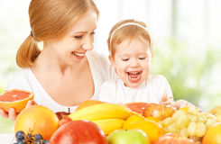 Happy family mother and daughter little girl, eat healthy vegetarian food, fruit. Happy family mother and daughter little girl, eat healthy vegetarian food, lots royalty free stock images