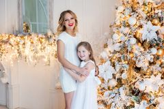 Mother and daughter near a Christmas tree Royalty Free Stock Images