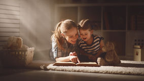 Happy family mother and daughter read a book in evening Stock Photos