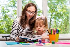 Happy family. Mother and daughter reading a book, homework. Happy family. Mother and daughter together paint. Mom and daughter reading a book, homework. Woman Royalty Free Stock Photo