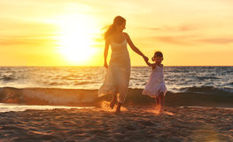Happy family  mother and daughter run, laugh and play at beach Stock Images