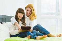 Happy family. Mother and daughter sitting on the bed with a tablet Stock Images