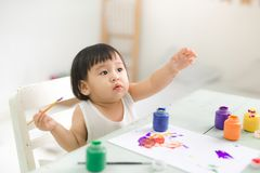 Happy family mother and daughter together paint. Asian woman helps her child girl. stock photo