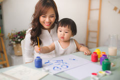 Happy family mother and daughter together paint. Asian woman helps her child girl. royalty free stock photo