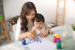 Happy family mother and daughter together paint. Asian woman helps her child girl. royalty free stock image