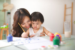Happy family mother and daughter together paint. Asian woman helps her child girl. stock photos