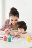 Happy family mother and daughter together paint. Asian woman helps her child girl. stock photography