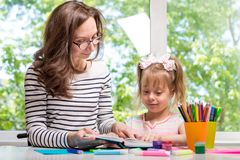 Happy family. Mother and daughter reading a book, homework. Happy family. Mother and daughter together paint. Mom and daughter reading a book, homework. Woman Stock Image