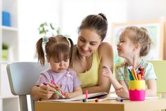Mother and kids daughters are learning to write. Adult woman teaches children writing. Happy family. Mother and daughters are learning to write Royalty Free Stock Photography