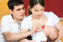 Happy family - mother, father and baby. Happy family home: father, mother and baby sitting on the floor in living room Stock Image