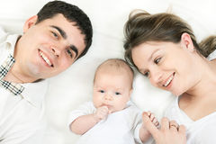 Happy family - mother, father and baby. Happy family home: father, mother and baby lying on the bed and playing stock images