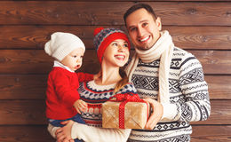 Happy family mother, father and baby with Christmas gifts on woo Stock Image