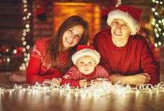 Happy family mother father and baby at christmas tree at home Royalty Free Stock Image