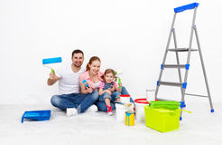 Happy family mother father and baby daughter are doing repairs p Stock Photos