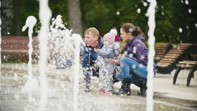 Happy Family - mother, Father and baby daughter near fountains in the city park, slow motion stock footage