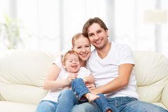 Happy family mother, father, child baby daughter at home on  sofa playing and laughing Stock Photos