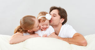 Happy family mother, father, child baby daughter at home on  sofa playing and laughing Stock Image