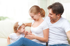 Happy family mother, father, child baby daughter at home on  sofa playing and laughing Stock Photography