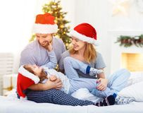Happy family mother father and child on Christmas morning in bed. In pajamas open gifts Stock Photography