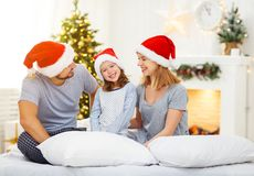 Happy family mother father and child on Christmas morning in bed. In pajamas open gifts Royalty Free Stock Images