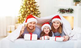 Happy family mother father and child on Christmas morning in bed Royalty Free Stock Photos