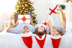 Happy family mother father and child on Christmas morning in bed Royalty Free Stock Image