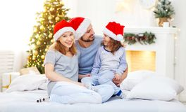 Happy family mother father and child on Christmas morning in bed Stock Image