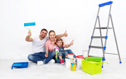 Happy family mother father and child daughter are doing repairs Stock Images