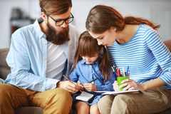 Happy family mother father and child daughter draw at home on couch royalty free stock images