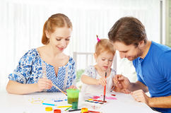 Happy family: mother, father and child  daughter draw paints Stock Images