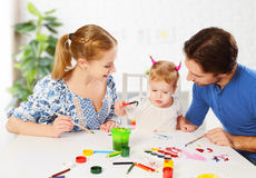 Happy family: mother, father and child daughter draw paints Royalty Free Stock Photo