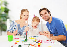 Happy family: mother, father and child daughter draw paints Royalty Free Stock Photography