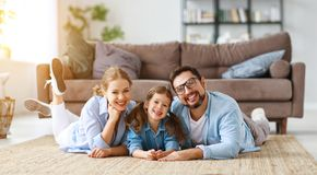 Happy family mother father and child daughter at home on couch stock photo