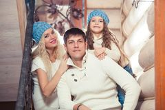 Happy family mother, father, child daughter at home, in a winter sweater and hat, the concept of Christmas. on the. Stairs Stock Photo