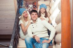 Happy family mother, father, child daughter at home, in a winter sweater and hat, the concept of Christmas. on the. Stairs Royalty Free Stock Image
