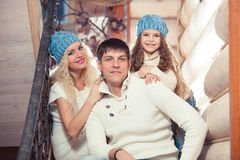 Happy family mother, father, child daughter at home, in a winter sweater and hat, the concept of Christmas. on the. Stairs Royalty Free Stock Photos
