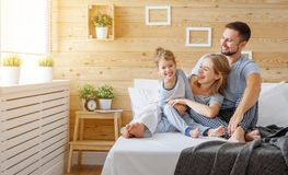 Happy family mother, father and child   laughs in bed Royalty Free Stock Image
