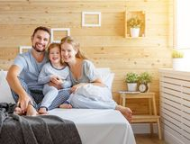 Happy family mother, father and child   laughs in bed Royalty Free Stock Photos