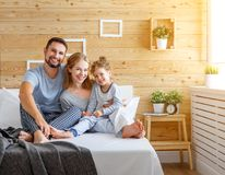 Happy family mother, father and child   laughs in bed Stock Images