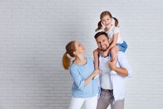 Happy family mother father and child  near an empty brick wall. Happy family mother father and child daughter near an empty brick wall Stock Photo
