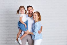 Happy family mother father and child  near an empty brick wall. Happy family mother father and child daughter near an empty brick wall Stock Photography
