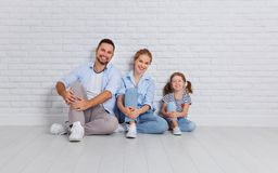 Happy family mother father and child  near an empty brick wall. Happy family mother father and child daughter near an empty brick wall Royalty Free Stock Photo