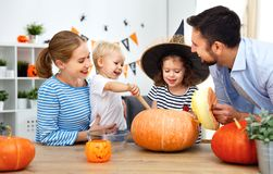 Happy family mother father and children cut pumpkin for   hallow Stock Photos
