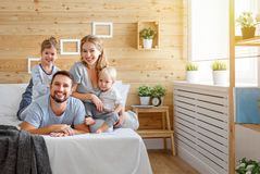 Happy family mother father and children daughter and son in bed. Bedroom Stock Photo
