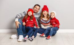 happy family mother, father and children in knitted hats and sweaters on gray background stock image